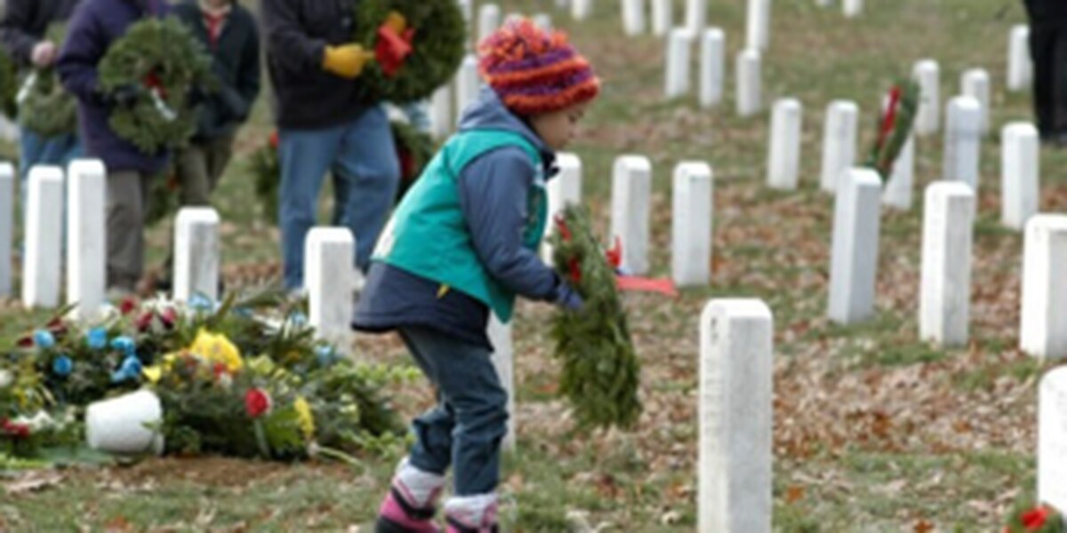 young girl in winter clothes - red hat and blue jacket - laying a Christmas wreath on a fallen solider's grave