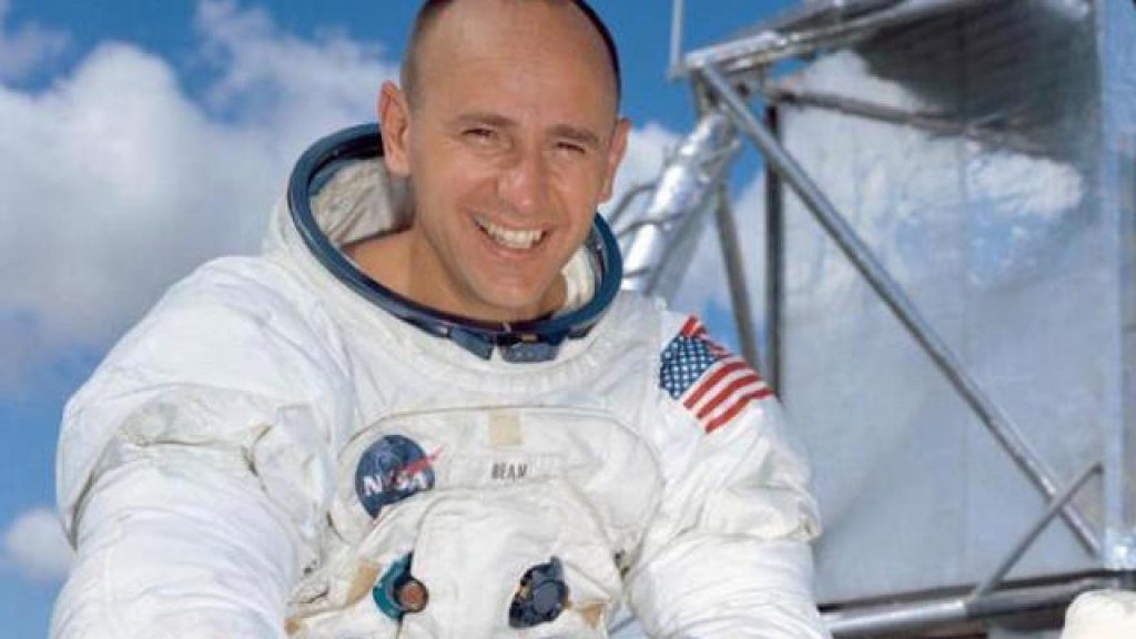 Blue sky with white cloud background, edge of moon landing space shuttle with Alan Bean in the foreground in his astronaut gear.